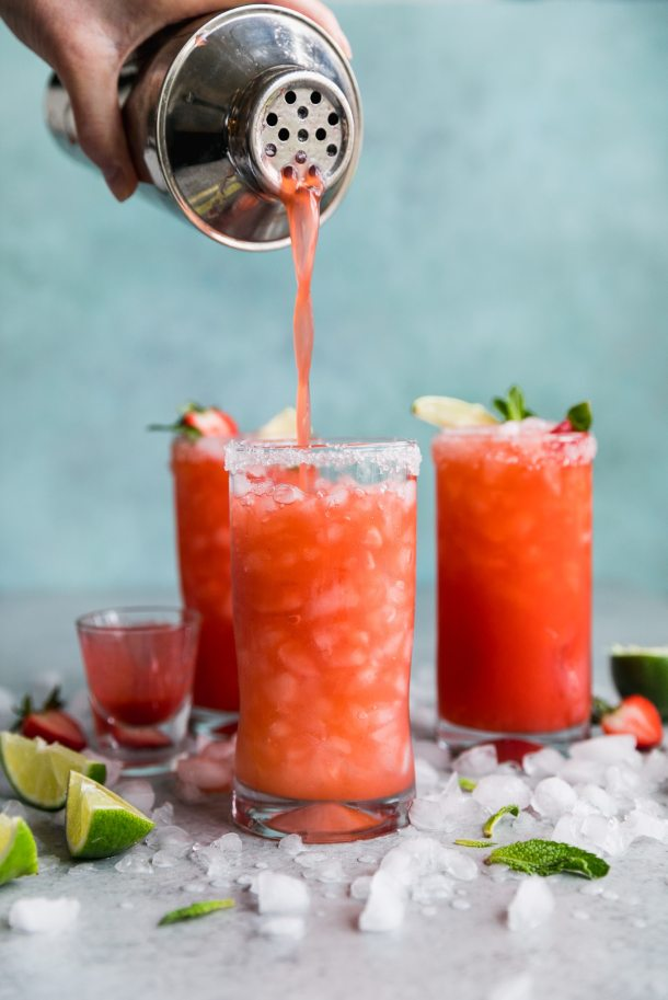 Shot of a strawberry margarita being poured from a shaker into a tall glass with two margaritas in the background