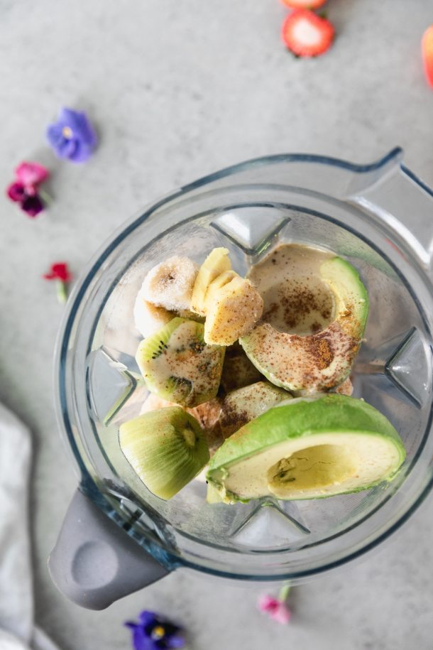 Overhead shot of a blender filled with a halved avocado, frozen banana pieces, a halved kiwi, cinnamon, and tahini, with edible flowers scattered next to it