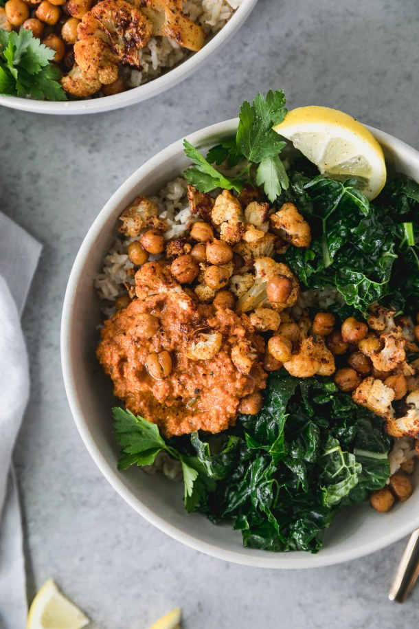 Overhead close up shot of a bowl filled with brown rice, sautéed kale, roasted chickpeas, cauliflower, a scoop of romesco sauce, and a lemon wedge