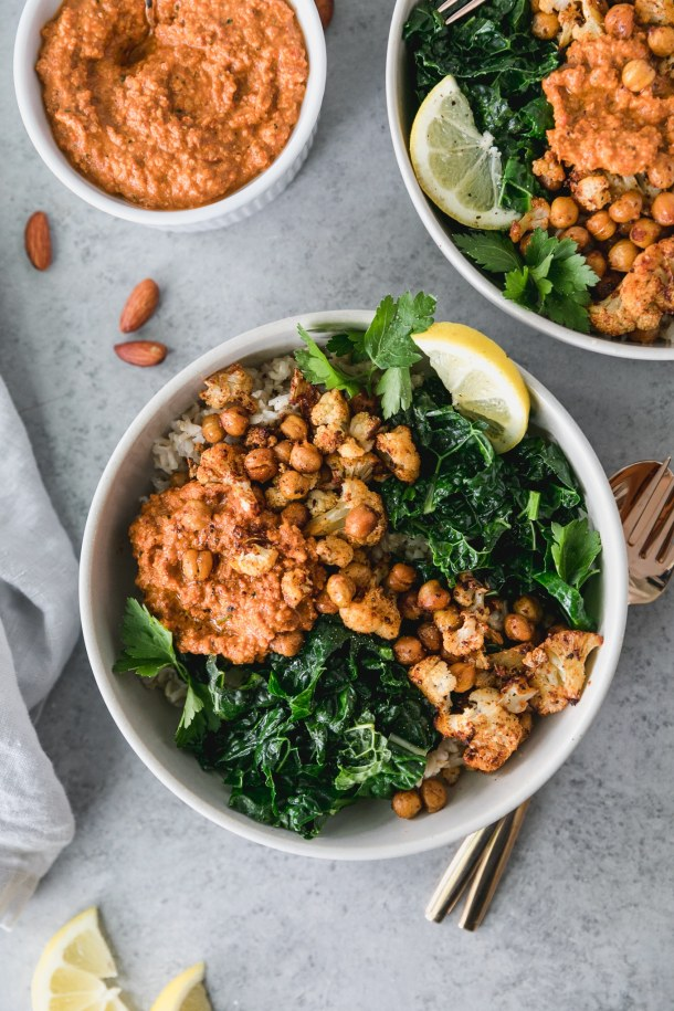 Overhead shot of two bowls of sautéed kale with roasted chickpeas and cauliflower, with a scoop of romesco sauce and another bowl of romesco off to the left