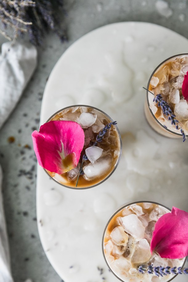 Overhead shot of 3 iced lattes topped with rose petals and lavender sprigs with water puddles on the marble board they're sitting on