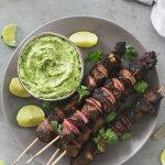 Overhead shot of a grey plate with steak skewers and a bowl of avocado salsa verde on it, with cilantro leaves and lime wedges scattered around