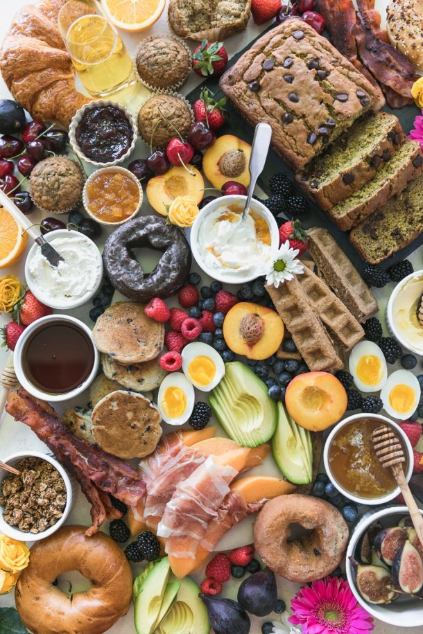 Overhead shot of a colorful brunch board filled with doughnuts, muffins, chocolate chip banana bread, fruit, mini pancakes, waffle sticks, yogurt, prosciutto wrapped melon, avocado, soft boiled eggs, bacon, granola, and bagels
