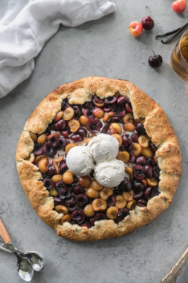 Overhead shot of a cherry galette with 3 scoops of ice cream on top