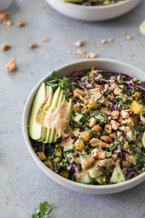 Close up shot of a crunchy vegetable salad with sliced avocado and cashews on top
