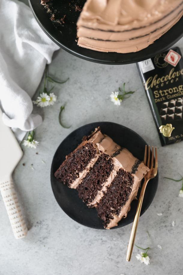 Overhead shot of a piece of chocolate cake on a black plate with a fork resting on the plate and a chocolate bar next to it