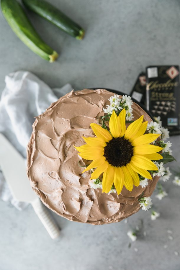 Overhead shot of a chocolate cake topped with a sunflower and small white flowers
