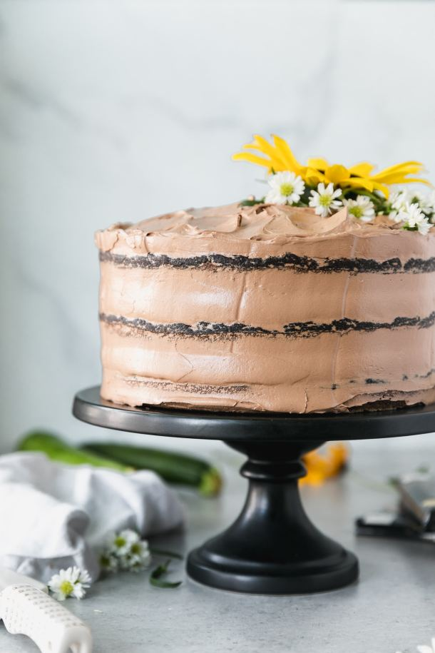 Forward facing shot of a 3 layer chocolate cake topped with a sunflower and small white flowers and a napkin and a zucchini in the background