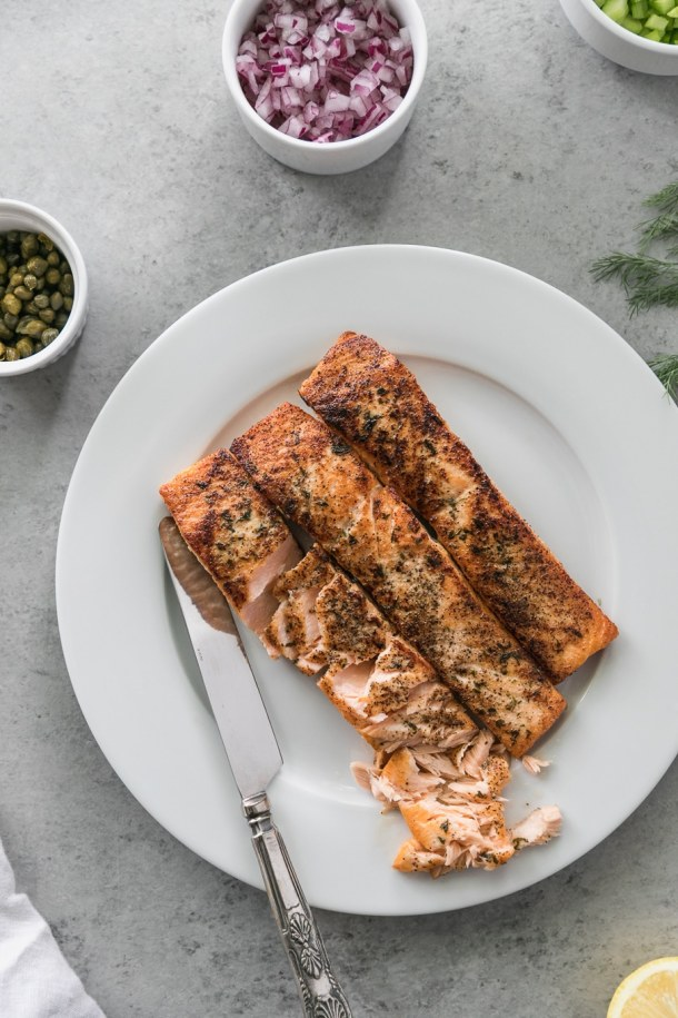 Overhead shot of a plate of 3 salmon fillets, a bowl of diced red onion, a bowl of capers, and dill