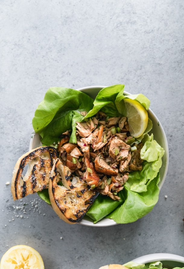 Overhead shot of a bowl of butter lettuce topped with flaked salmon, grilled garlic bread, and a lemon wedge