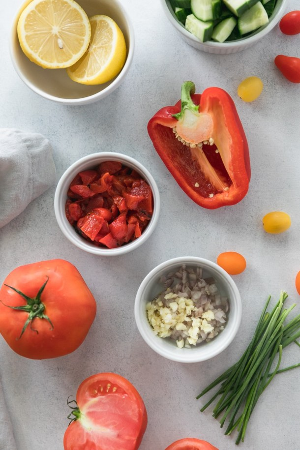 Overhead shot of a bowl filled with a halved lemon, a bowl of diced cucumber, a halved bell pepper, a bowl of chopped roasted red peppers, a bowl of chopped shallot and garlic, a large tomato, chives, and cherry tomatoes scattered around