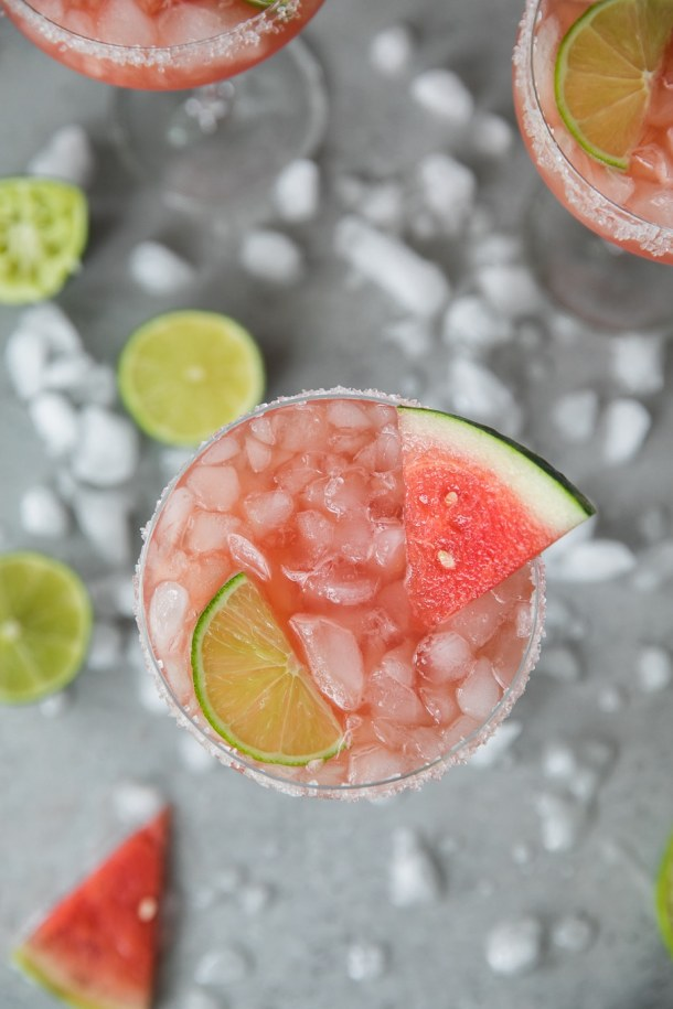 Overhead shot of a tall margarita glass filled with a watermelon grapefruit margarita, garnished with a slice of watermelon and lime