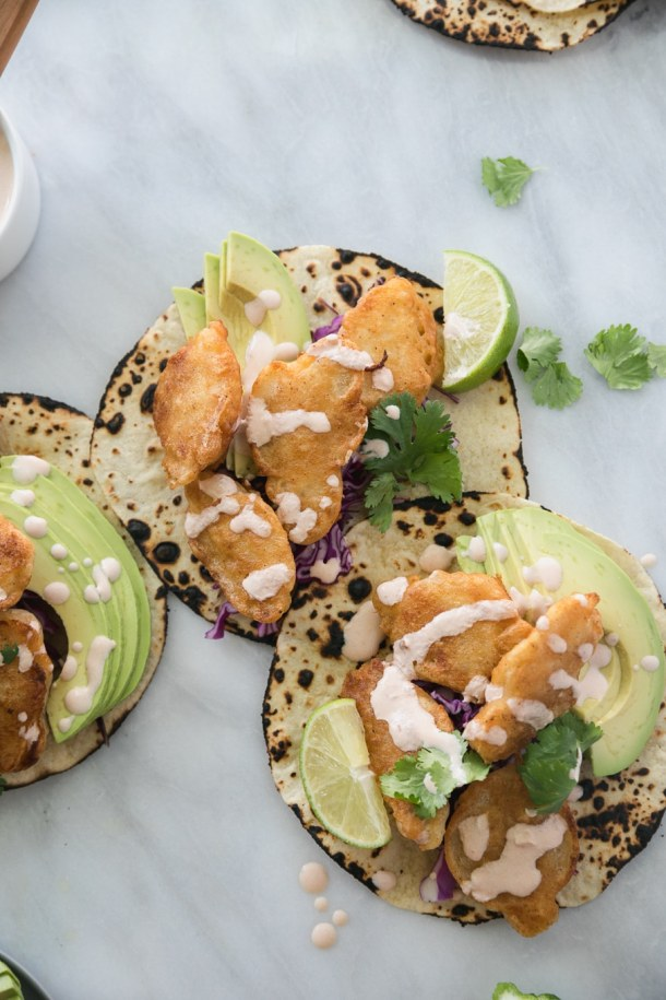 Overhead shot of 3 crispy fish tacos topped with avocado, cilantro, and chipotle lime crema