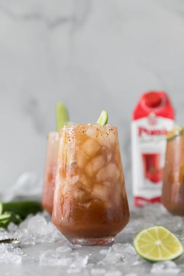 Forward facing shot of 3 michelada cocktails with lime wedges and cucumbers sticking out of them