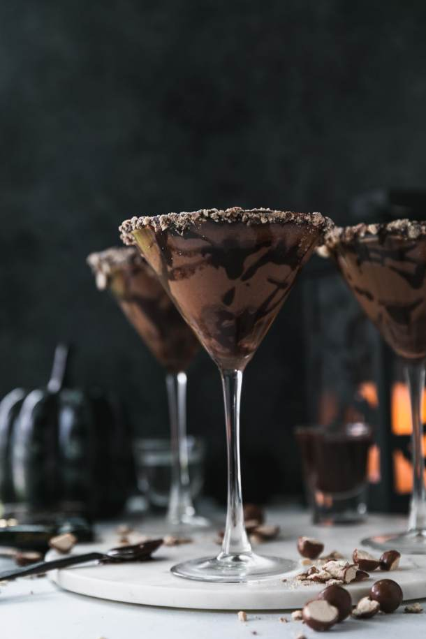Forward facing shot of 3 chocolate martinis with a black background and black and orange glowing lantern in the background with crushed malted milk ball candy scattered next to the martinis