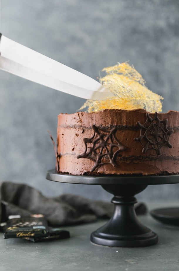 Forward facing shot of a large knife getting ready to cut into a chocolate cake with dark chocolate spider webs on it and a spun sugar cobweb on top