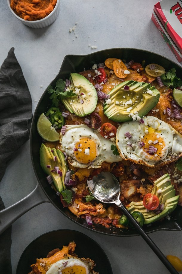 Overhead shot of a skillet of chilaquiles with a spoon resting in the skillet where some has been scooped out