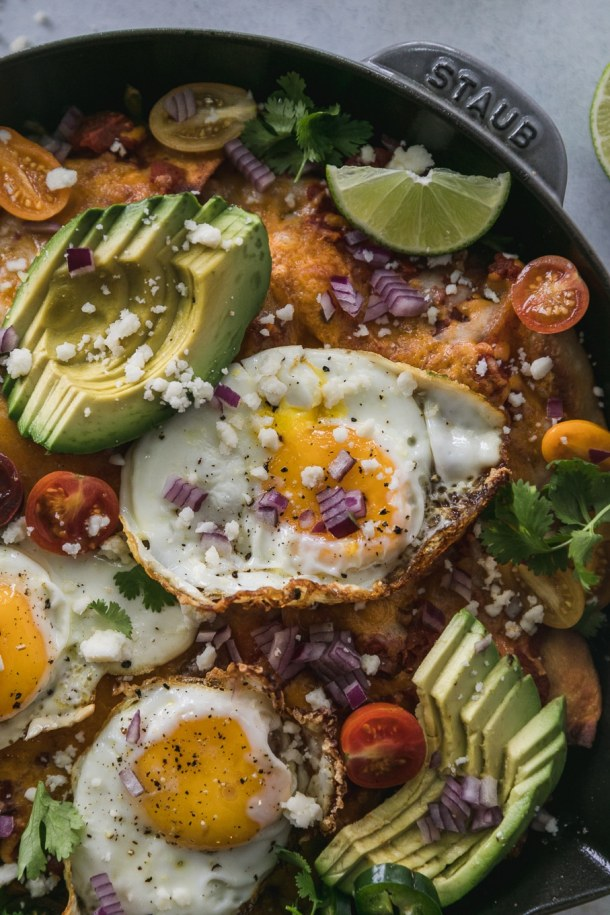 Close up shot of chilaquiles topped with a fried egg, sliced avocado, lime wedges, sliced tomatoes, and chopped red onion