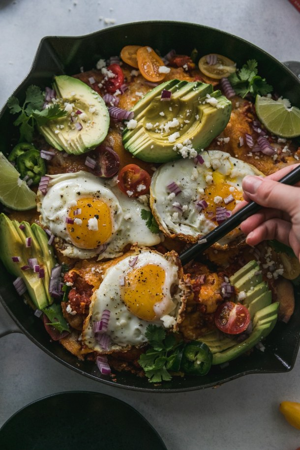 Overhead shot of a spoon scooping out chilaquiles and a fried egg from the pan