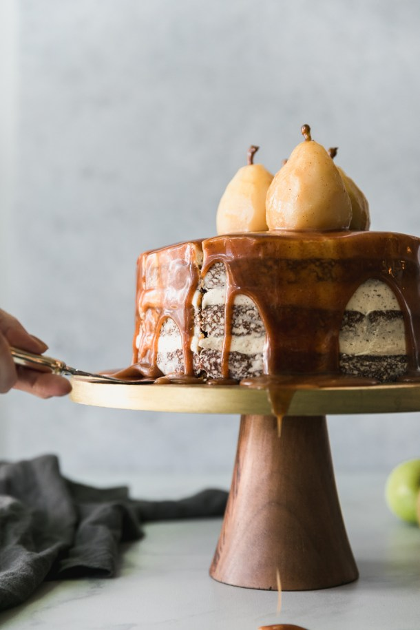 Forward facing shot of a layer cake dripping in caramel, topped with poached pears, on a gold and wooden pedestal, with a slice about to be pulled out
