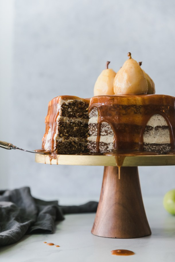 Forward facing shot of a layer cake dripping in caramel, topped with poached pears, on a gold and wooden pedestal, with a slice being taken out