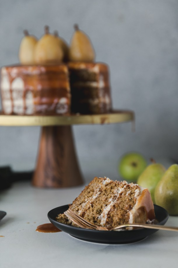 Shot of a slice of cake on a black plate with a layer cake on a gold and wood pedestal in the background topped with poached pears
