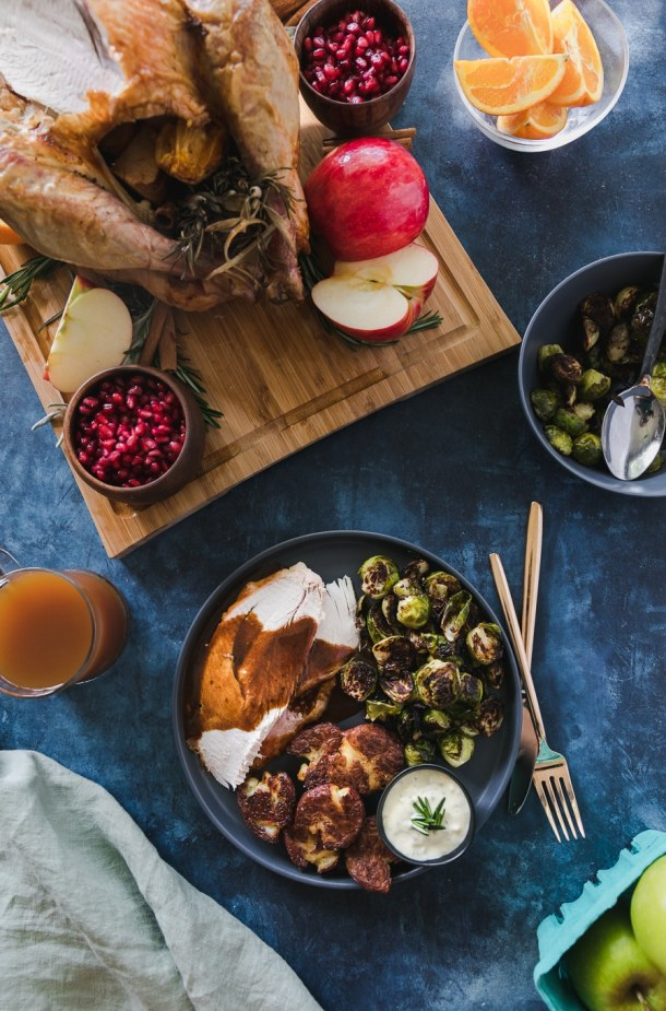 Overhead shot of a plate with turkey and gravy, roasted brussels, roasted smashed potatoes, and aioli against a blue background with the whole roasted turkey on a wooden cutting board above the plate
