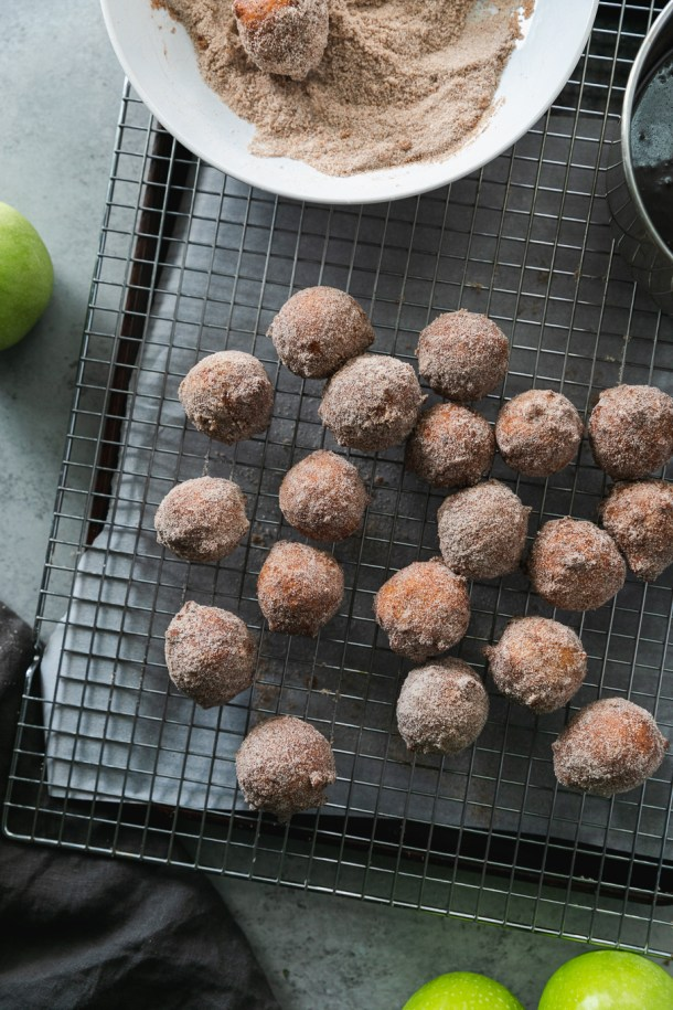 Overhead shot of a cooling rack with doughnut holes on top and a green apple next to it