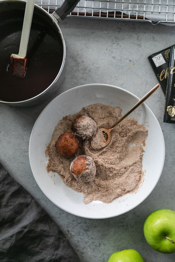 Overhead shot of a white shallow bowl filled with cinnamon sugar, doughnut holes, and a gold spoon