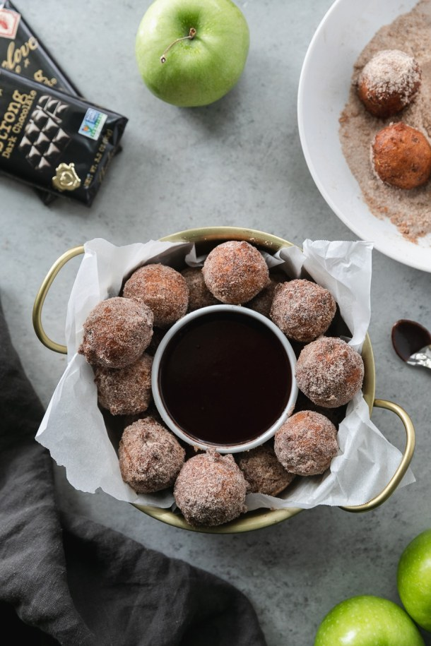 Overhead shot of a gold bowl with handles filled with doughnut holes and a ramekin of dark chocolate fudge sauce and chocolate bars above it