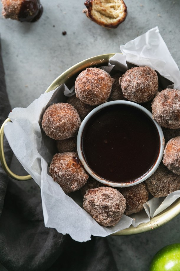 Overhead close up shot of a gold bowl with handles filled with doughnut holes and a ramekin of dark chocolate fudge sauce