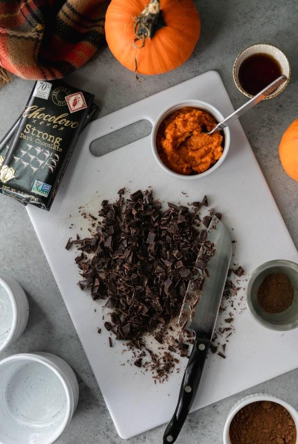 Overhead shot of a cutting board with chopped chocolate on it, a ramekin of pumpkin purée, chocolate bars, a ramekin of pumpkin pie spice, and mini pumpkins