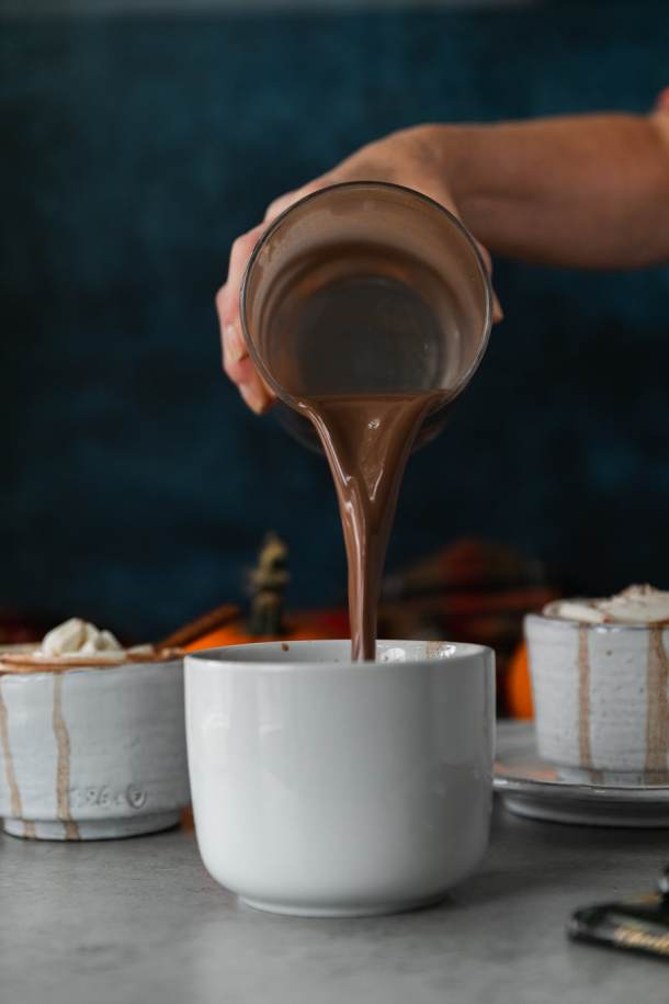 Forward facing action shot of a white mug with hot chocolate being poured into it out of a clear glass