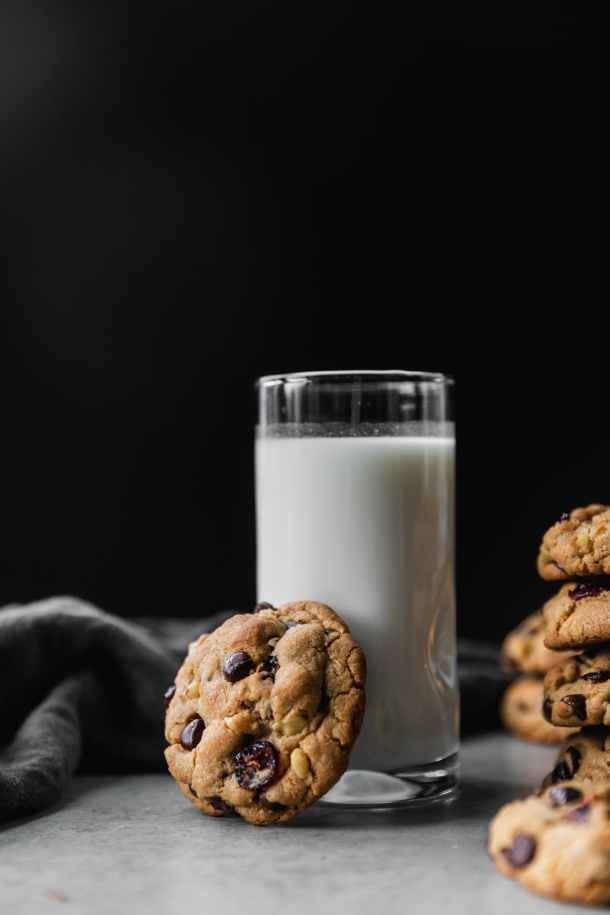 Shot of a glass of milk against a black background with a dark chocolate cranberry walnut cookie resting up against it