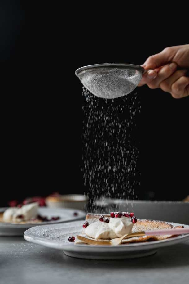 Forward facing shot of a hand dusting powdered sugar onto a dutch baby pancake on a white plate with whipped cream and pomegranate arils against a black background