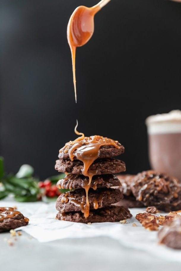 Forward facing shot of a stack of chocolate cookies being drizzled with salted caramel with a glass of hot chocolate against a black background with holly in the background