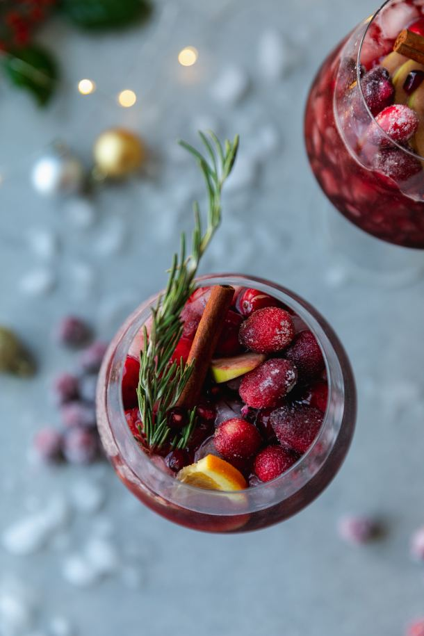 Overhead shot of a wine glass filled with red sangria, sugared cranberries, orange slices, a cinnamon stick, and a rosemary sprig