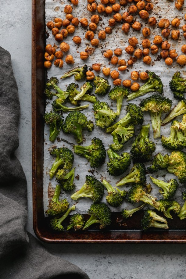 Overhead shot of a rimmed baking sheet filled with roasted broccoli and roasted chickpeas