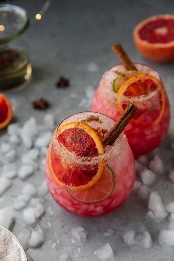 Close up shot of a pink blood orange cocktail garnished with a slice of blood orange and a cinnamon stick with another cocktail behind it