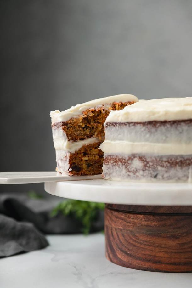 Forward facing close up shot of a carrot cake on a marble and wooden cake stand with a slice being taken out of the cake
