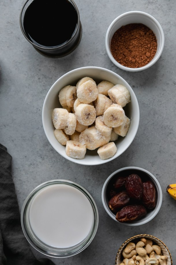 Overhead shot of a ramekin of maple syrup, a ramekin of cocoa powder, a bowl of frozen bananas, a ramekin of dates, and a jar of cashew milk against a grey background