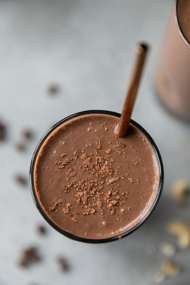 Overhead close up shot of a chocolate mocha smoothie with a star sticking out of it and cocoa powder dusted on the top of the smoothie