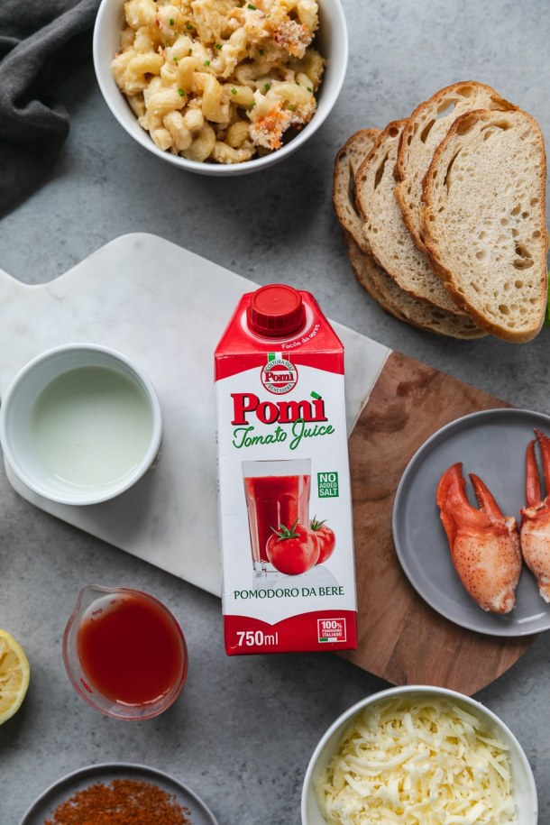 Overhead shot of a carton of pomp tomato juice on a wooden and marble board with a plate of lobster claw meat next to it, and sliced of bread and a bowl of mac and cheese above it