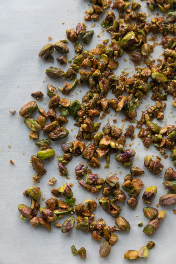 Overhead close up shot of candied pistachios against a white parchment background