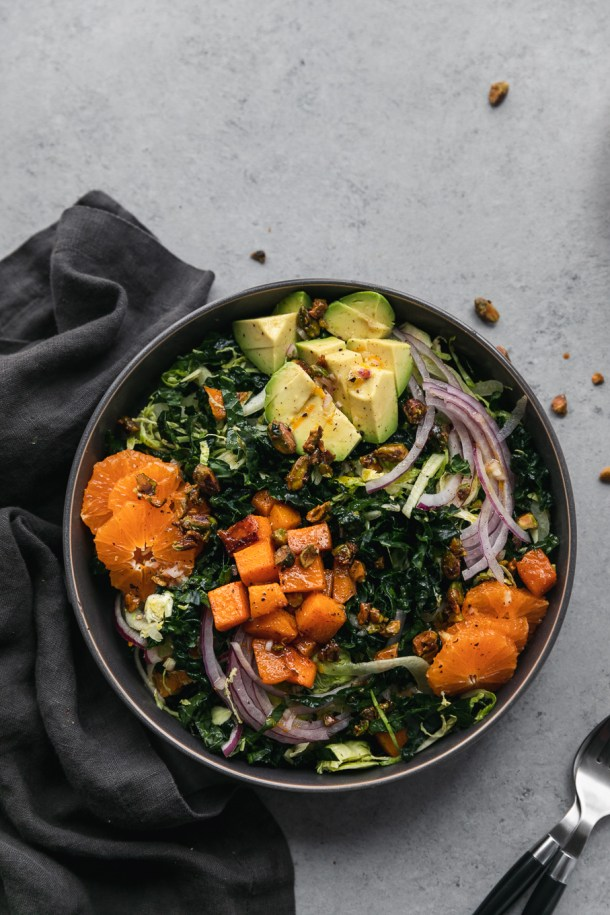 Overhead shot of a kale salad with avocado, mandarins, red onion, butternut squash, and candied pistachios with a dark grey napkin next to it