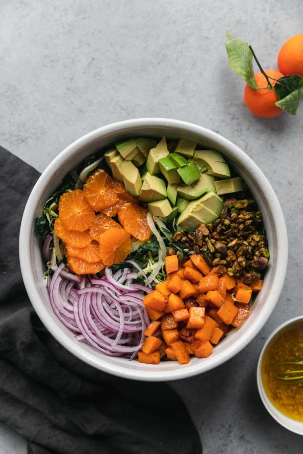 Overhead shot of a large white bowl filled with kale, shaved brussels, a pile of mandarins, diced avocado, candied pistachios, butternut squash, and sliced red onion all arranged on top