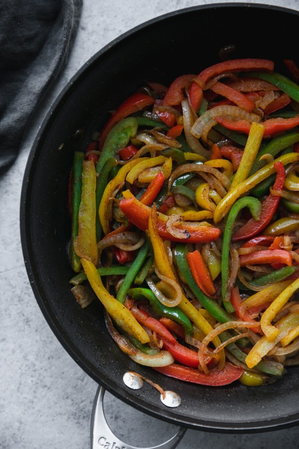 Overhead shot of a black skillet filled with sautéed peppers and onions