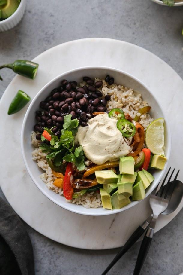 Overhead shot of a burrito bowl filled with brown rice, black beans, fajita veggies, avocado, lime, cilantro and cashew queso