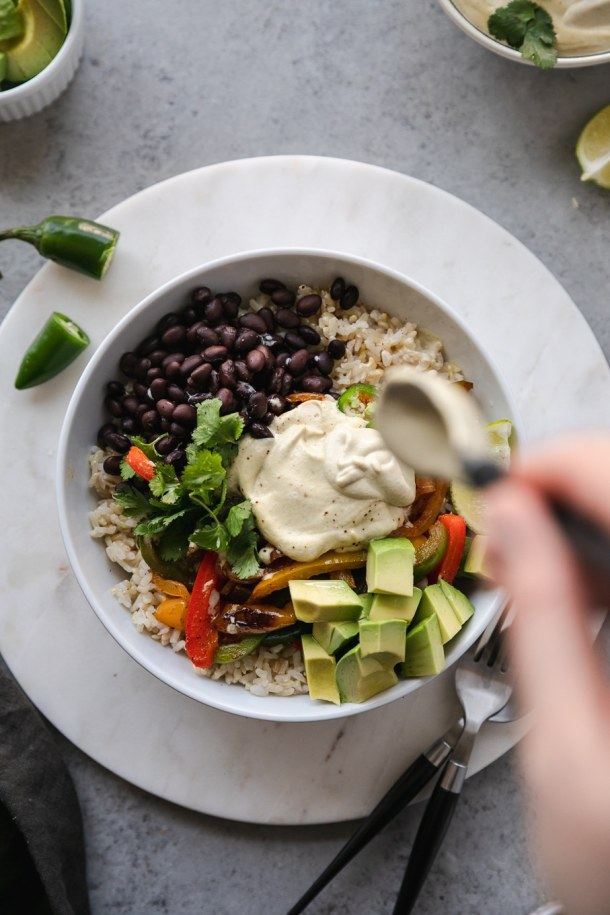 Overhead shot of a burrito bowl filled with black beans, fajita veggies, and avocado, being drizzled with cashew queso