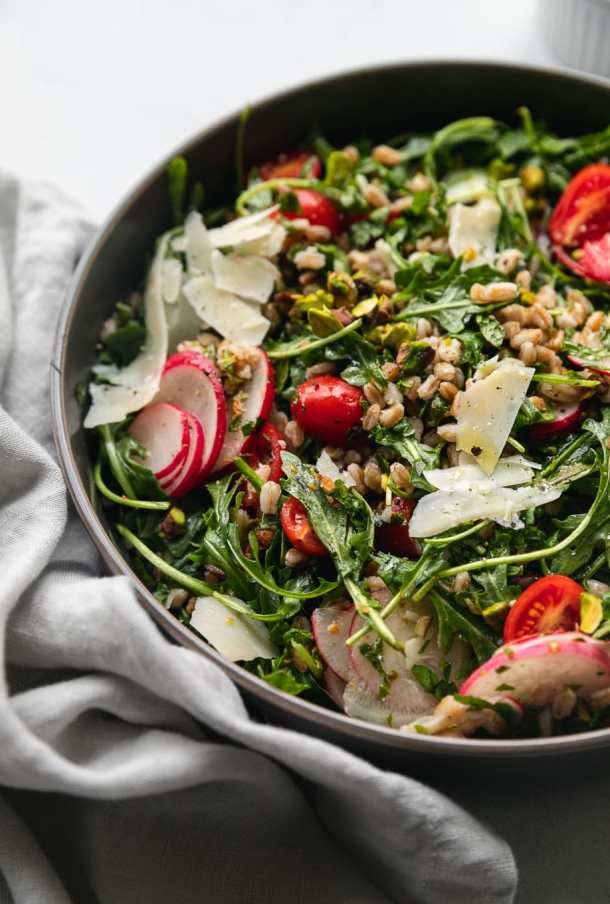 Close up shot of a farro arugula salad topped with tomatoes, sliced radishes, shaved parmesan, and chopped pistachios